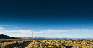 Power line and open field Royalty Free Stock Photos