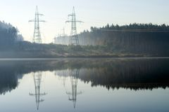 Power line passes over the lake. Morning shot in the haze on the background of the forest royalty free stock photo