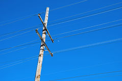 Power Line Pole and Half moon. A power line pole in front of a vivid blue sky. In between the lines is a half moon Royalty Free Stock Photo