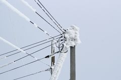Power line on a pole of many wires covered with a thick layer of snow.  stock photos