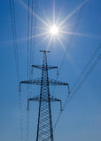 Power Line. pylon against a blue sky and sun. Power Line. pylon against a blue sky and sun Royalty Free Stock Photography