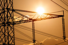 Power line pylon and sun Royalty Free Stock Photos