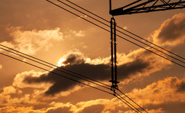 Power line pylon and sun Stock Images