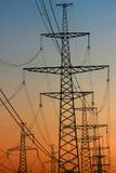 Power line pylons against sunset sky background Stock Photos