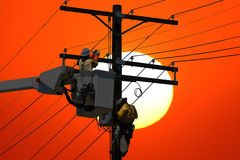 Power Line Repair. Utility workers repair a power line at sunset Royalty Free Stock Images