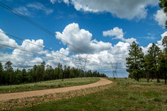 Power line road with storm clouds. Royalty Free Stock Image