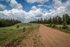 Power line road with storm clouds. Royalty Free Stock Images
