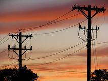 Power Line Silhouette. Power lines silhouetted against a red sunset Royalty Free Stock Image