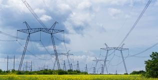Power line summer landscape. / passing overhead electricity wire of the support carrying the light and the heat in the house royalty free stock image
