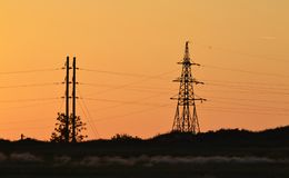 Power line at sunset, sunset against a backdrop of a futuristic landscape stock photos