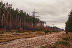 Power line tower along the dirt road near the autumn forest. Cloudy day Stock Photo