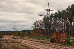 Power line tower along the dirt road near the autumn forest. Cloudy day Royalty Free Stock Image