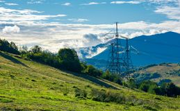 Power line tower on the hill. Huge mountain in clouds in the distance. autumn countryside Royalty Free Stock Photo