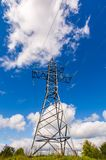 Power line tower on the hill. View from below. beautiful blue sky with clouds Royalty Free Stock Image