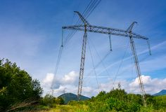 Power line tower on a hillside. Giant metal construction in beautiful landscape. power and energy concept Stock Image