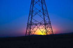 Power line tower and sunrise Royalty Free Stock Photo