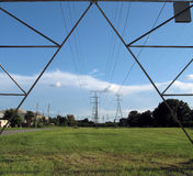Power line and towers. A view of green grass field with power transmission lines and towers passing along a residential area. Taken through the legs of a Royalty Free Stock Photos