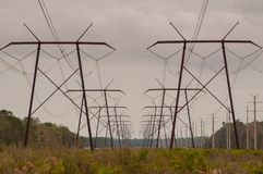 Row of electric power lines towers in perspective royalty free stock image