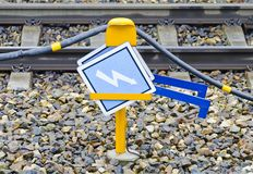 Power line for trains with attention signs Stock Photos