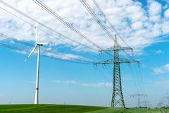 Power line and wind turbine royalty free stock photo