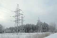Power line. In the winter snowy forest, sombre sky Stock Photos