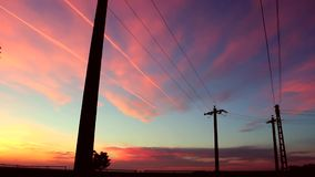 Power line and sunset. Power line with wires on the background of the evening sky with pink clouds stock video