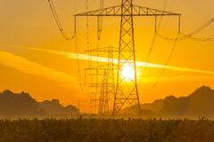 Power line in a yellow sky at sunrise. In summer Royalty Free Stock Image