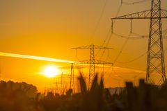 Power line in a yellow sky at sunrise. In summer Stock Photo