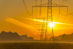 Power line in a yellow sky at sunrise. In summer Royalty Free Stock Photo