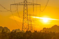 Power line in a yellow sky at sunrise Royalty Free Stock Photos