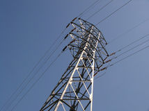 Power lines. A steel tower supports electrical wires against a clear blue sky Royalty Free Stock Photography