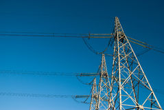 Power lines. Bottom-up view of power lines on the blue sky background Royalty Free Stock Images