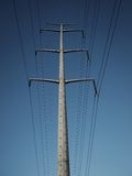 Power Lines. High tension power lines against a clear blue sky Royalty Free Stock Photo