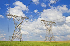 Power Lines. Super wide angle photograph of a row of power lines against a blue cloudy sky Royalty Free Stock Images