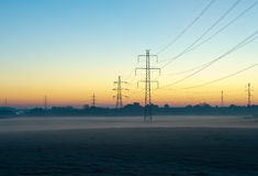 Power lines. Early misty morning by some pylons before sunrise Stock Photo