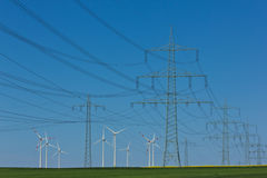 Power lines. Power line with blue sky and wind turbines Royalty Free Stock Photos