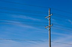 Power Lines. And one pole, against a lightly cloudy blue sky stock images