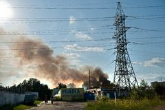 Power lines against the background of blue sky and black smoke on June 3, 2016 in Kiev Royalty Free Stock Photo