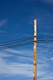 Power Lines against a Beautiful Sky. Power lines and post against a beautiful cloudy blue sky stock photo