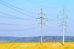 Power lines against blue sky Royalty Free Stock Photo