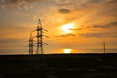 Power lines against rising sun Stock Photo