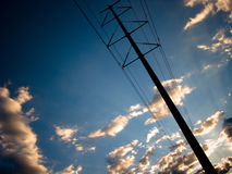 Power Lines against Sunset. Sunset with rays of light and small coouds with power line running diagonally Royalty Free Stock Images