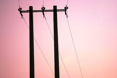 Power lines against sunset sky Stock Images