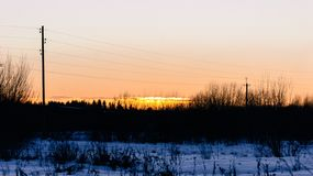 Power lines against a sunset in winter stock image