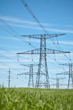 Power Lines with Blue Sky and Green Grass. Power lines running across a green field with blue sky in the background Stock Photography