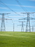 Power Lines with Blue Sky and Green Grass. Power lines and pylons running across a green field with blue sky in the background Royalty Free Stock Photos