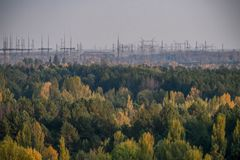 Power lines in the Chernobyl exclusion zone. Over the yellow-green autumn forest royalty free stock images