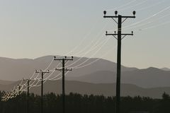 Power lines in the countryside. Overhead power lines in a remote area of Canterbury, New Zealand. Southern Alps in the background stock photography