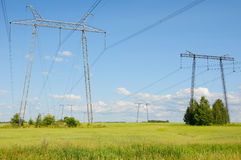 Power lines in the countryside against blue sky Stock Photos