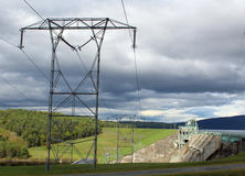 Power lines with a Dam in the background Royalty Free Stock Image